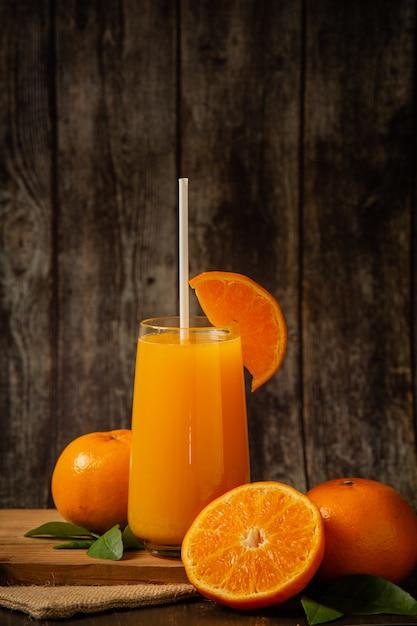 Succo d'arancia fresco in un bicchiere e arancia fresca Foto Gratuite