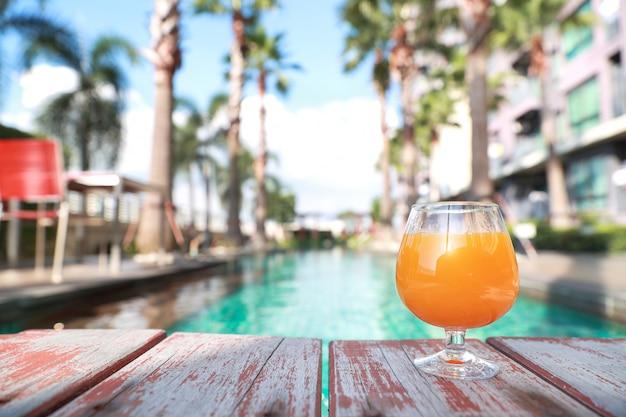 Succo d'arancia sulla piscina con lo spazio della palma e della copia Foto Premium