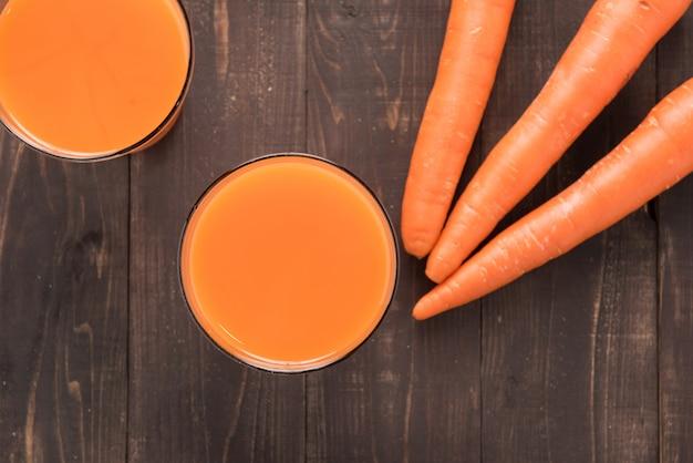 Succo di carota fresco del colpo superiore su fondo di legno Foto Premium