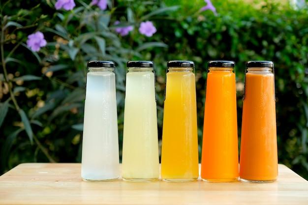 Succo di frutta organico freddo in bottiglia di vetro sulla tavola di legno al giardino. Foto Premium