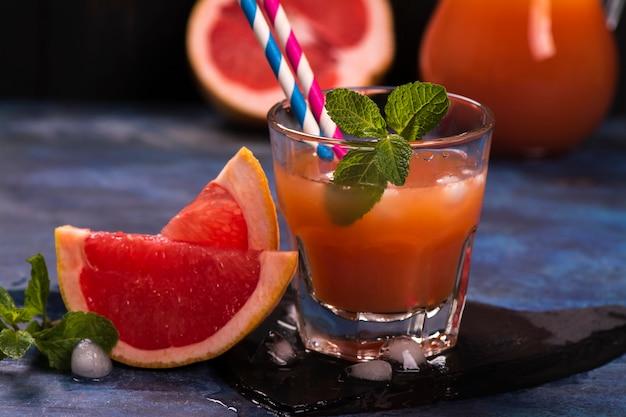 Succo di pomelo fresco con ghiaccio sopra fondo di legno scuro Foto Premium