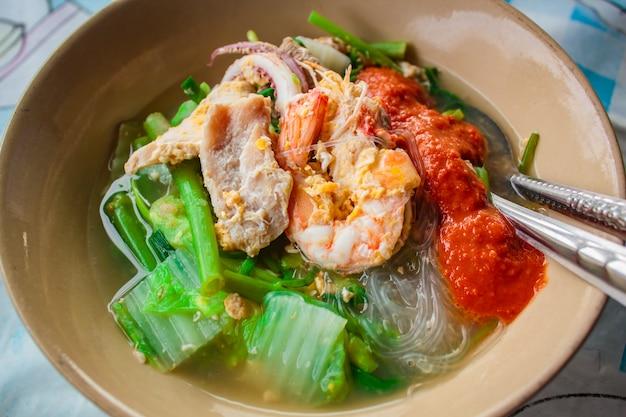 Suki in brodo misto di frutti di mare con vermicelli e verdure. Foto Premium