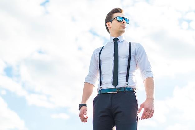 Sul tetto spiccano il giovane busunessman serio in camicia bianca, cravatta, bretelle e occhiali da sole Foto Premium