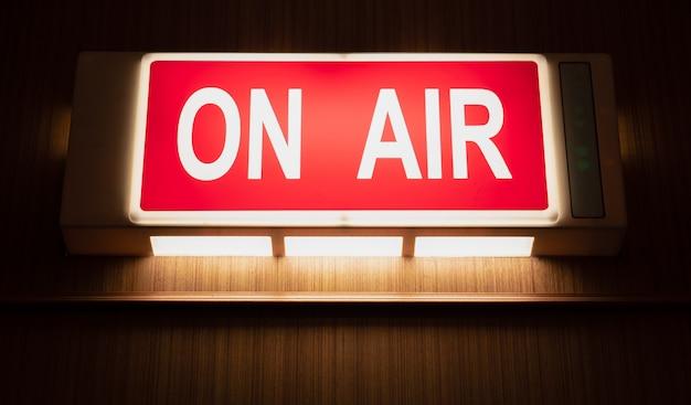 Sull'icona del segno di air che emette luce sulla parete di legno degli studi di registrazione del suono Foto Premium