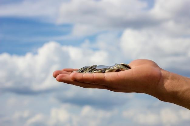 Sulla mano le monete sullo sfondo del cielo Foto Premium