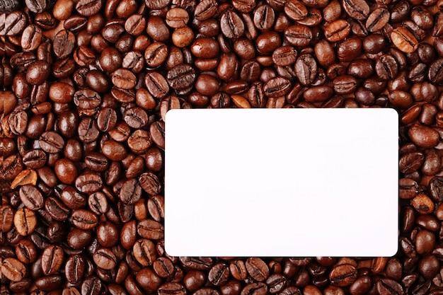 Sullo sfondo di chicchi di caffè c'è un biglietto da visita Foto Premium