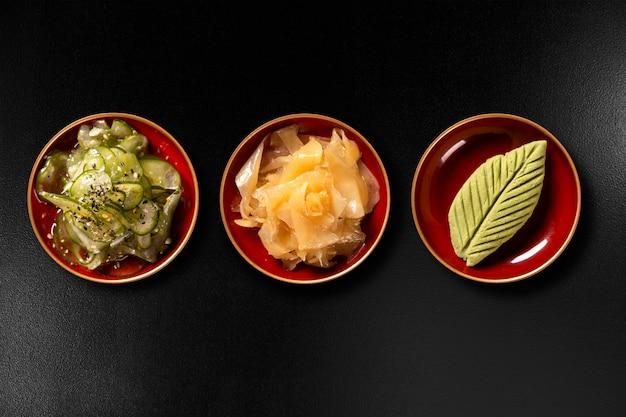 Sunomono, zenzero e wasabi isolati su sfondo nero. vista dall'alto. Foto Premium