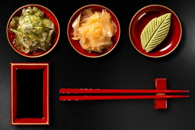 Sunomono, zenzero, wasabi, hashi e shoyu isolati su sfondo nero. vista dall'alto. Foto Premium