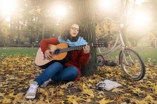 Suonando una chitarra in un parco Foto Premium