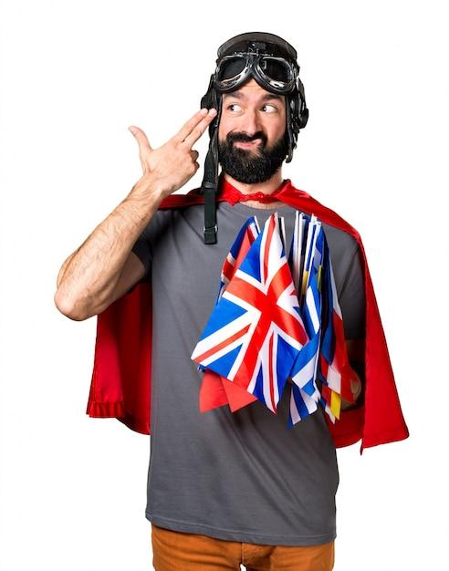 Superero con un sacco di bandiere che fanno un gesto suicida Foto Gratuite