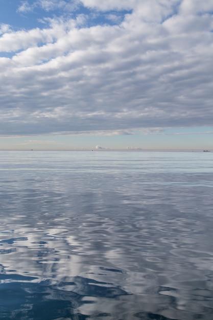 Superficie dell'acqua che riflette il cielo nuvoloso bianco Foto Gratuite