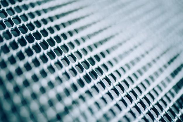 Superficie della recinzione metallica reticolare. acciaio inossidabile e alluminio sfocatura dello sfondo chiaro. trama macro Foto Premium
