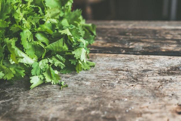 Superficie in legno con spazio per il testo con foglie di prezzemolo verde sul lato Foto Gratuite