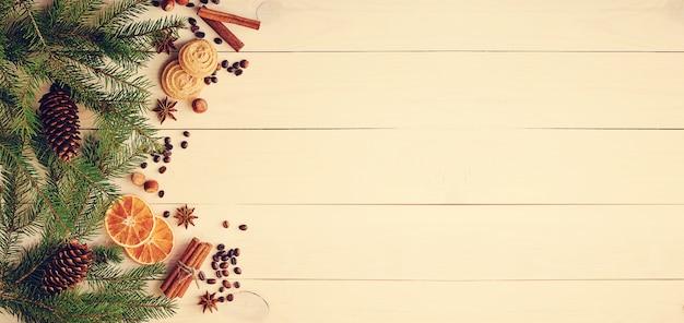 Superficie natalizia con rami di pelo, coni, arance secche, chicchi di caffè e anice stellato Foto Premium