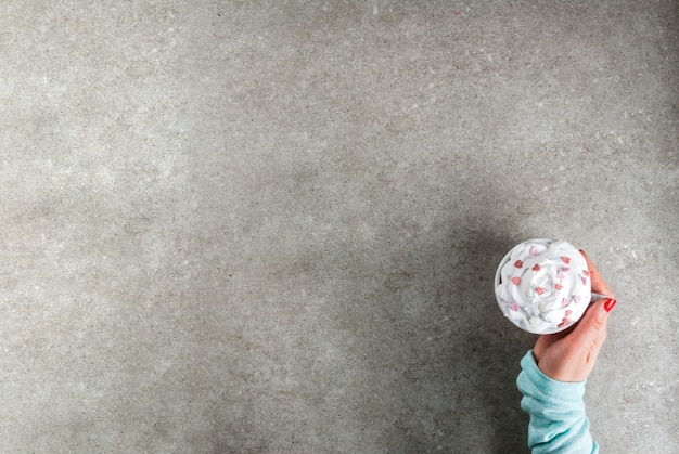 Superficie romantica, san valentino. ragazza che beve cioccolata calda con panna montata e cuori dolci, Foto Premium