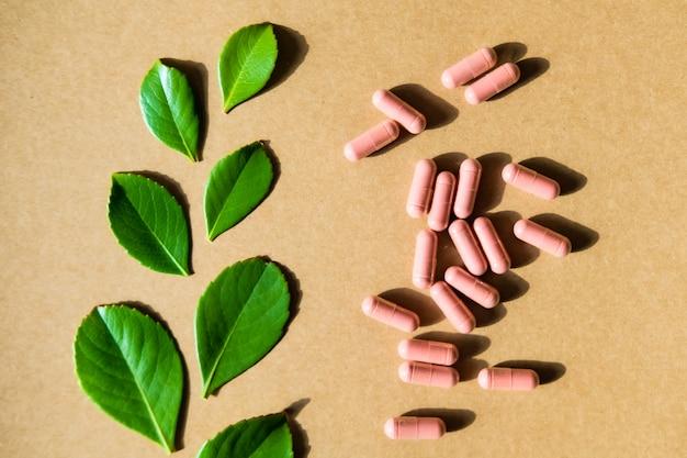 Supplemento di erbe in capsule marroni e foglie verdi Foto Premium