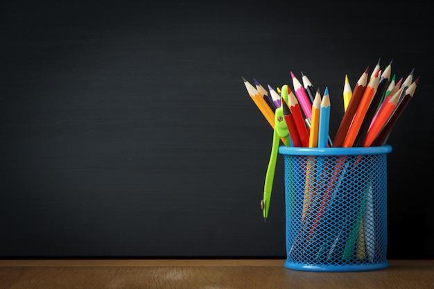 Supporto blu del primo piano con le matite della scuola sui precedenti di un grande bordo di gesso nero Foto Premium
