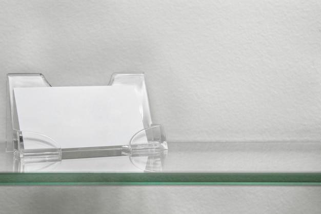 Supporto in carta acrilica per scheda vuota, supporto del biglietto da visita sulla mensola di vetro isolato Foto Premium