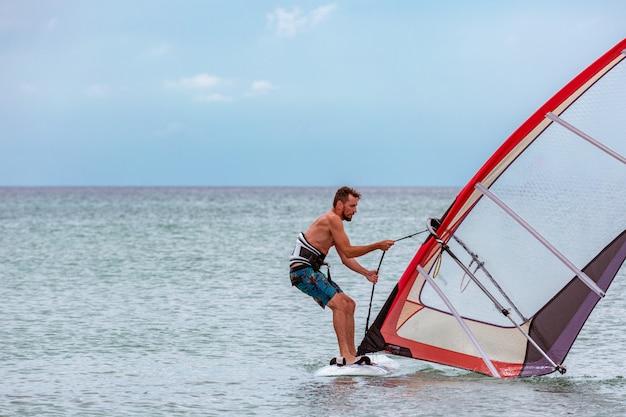 Surfista cavalca le onde in una bella giornata di sole. giovane che gode del vento e del surf sull'oceano. Foto Premium
