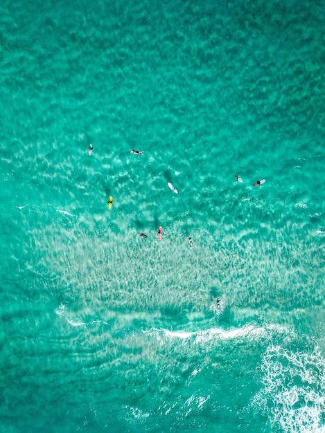Surfisti colpo verticale dall'alto con tavole da surf su un mare blu chiaro Foto Gratuite