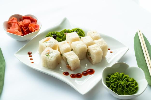 Sushi bianchi su un piatto bianco e superficie bianca con wasabi, zenzero e porcini Foto Premium