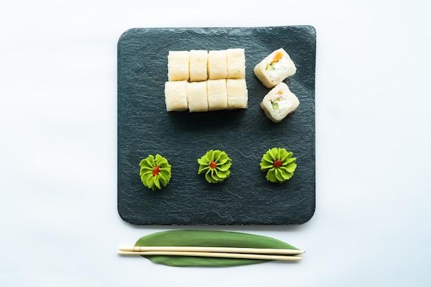 Sushi bianchi su una superficie nera e superficie bianca con wasabi e chopstocks Foto Premium