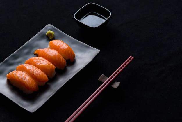 Sushi di color salmone con wasabi verde sulla banda nera o piatto e salsa shoyu su sfondo nero Foto Premium