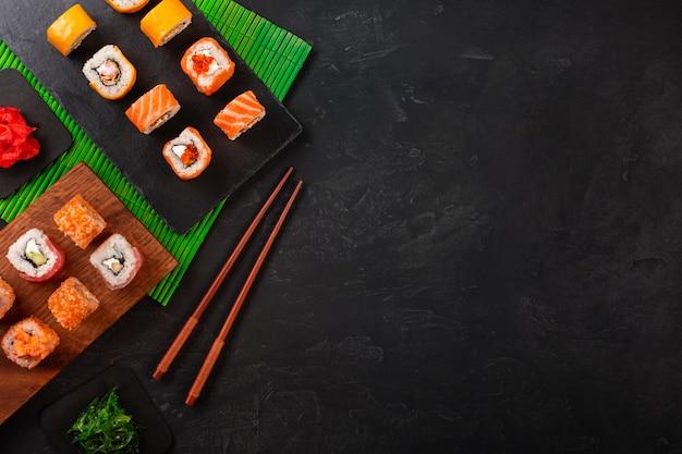Sushi set con wasabi e zenzero sul vassoio di pietra nera sul tavolo nero. vista dall'alto Foto Premium