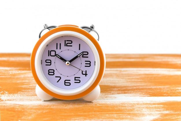 Sveglia bianca su un tavolo di legno arancione Foto Premium