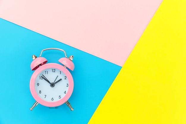 Sveglia classica suoneria a campana gemella isolata sulla parete geometrica variopinta pastello rosa giallo blu. ore di riposo tempo di vita buongiorno notte sveglia concetto sveglio. vista dall'alto. Foto Premium