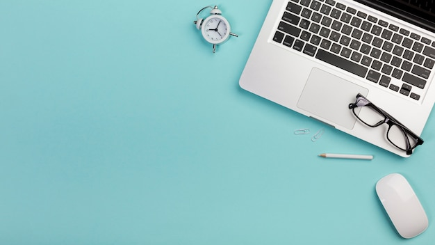 Sveglia, matita, occhiali, computer portatile, mouse sulla scrivania blu Foto Gratuite