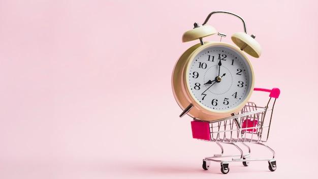 Sveglia nel carrello della spesa in miniatura su sfondo rosa Foto Gratuite