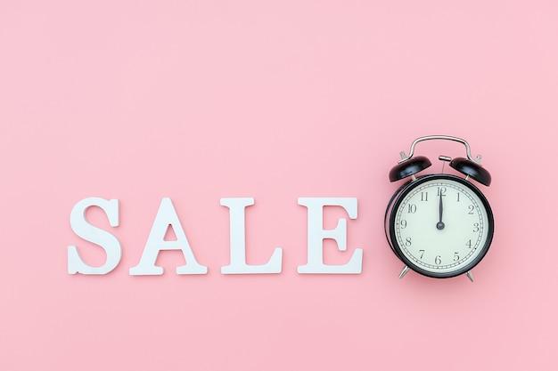 Sveglia nera e vendita del testo dalle lettere bianche del volume sul rosa Foto Premium