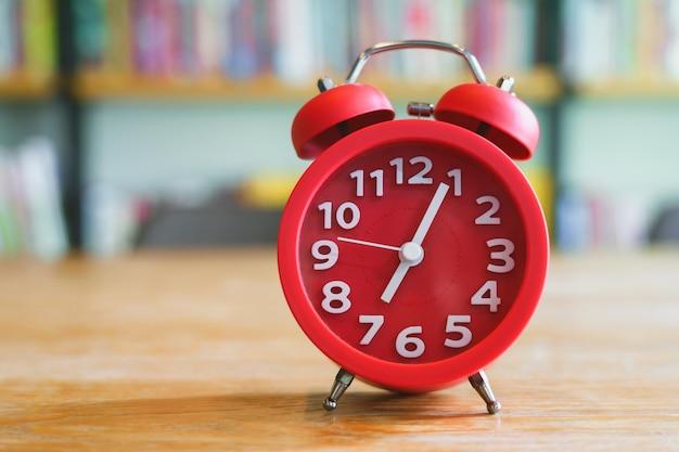 Sveglia rossa sulla tavola di legno nella stanza delle biblioteche o nel ministero degli interni. Foto Premium