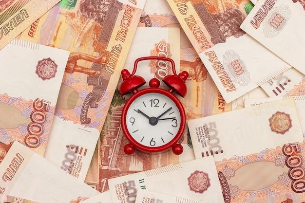 Sveglia rossa sullo sfondo di cinque millesimi bollette russo. concetto il tempo è denaro Foto Premium