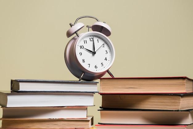 Sveglia sulla pila di scaffale per libri contro fondo colorato Foto Gratuite