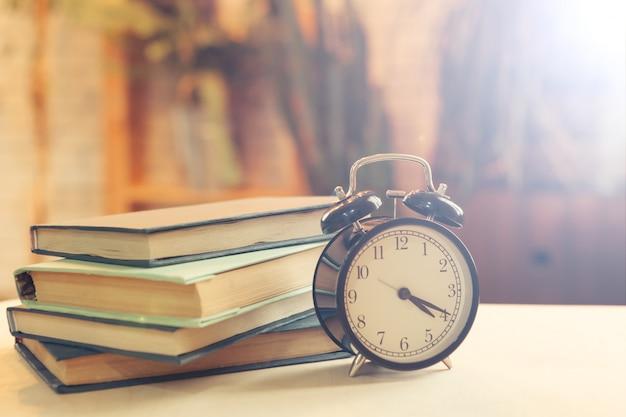 Sveglia vicino ai libri sul tavolo Foto Premium
