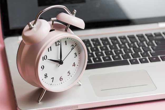 Sveglia vintage rosa su un computer portatile aperto Foto Gratuite