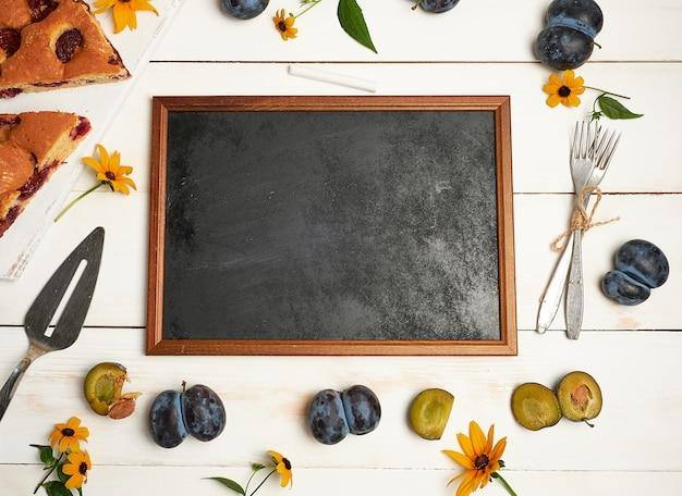 Svuotare gli ingredienti cornice gessosa nera e fette di plum cake Foto Premium