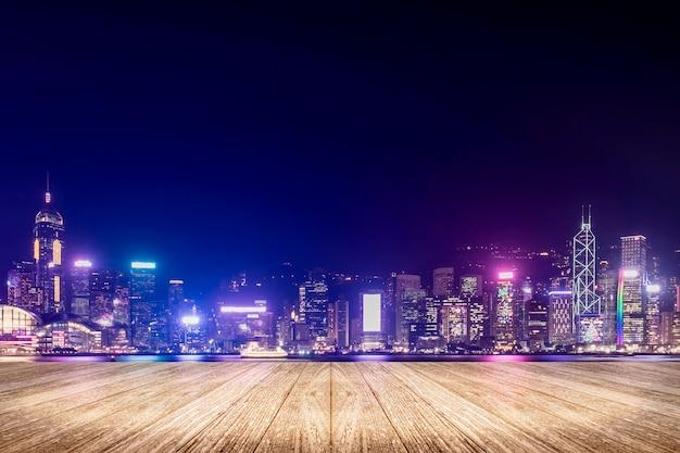 Svuoti il pavimento di legno della plancia con i fuochi d'artificio sopra paesaggio urbano al fondo di notte Foto Premium