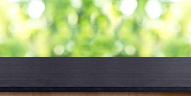 Svuoti il piano d'appoggio di legno nero con l'albero della sfuocatura in parco con bokeh Foto Premium