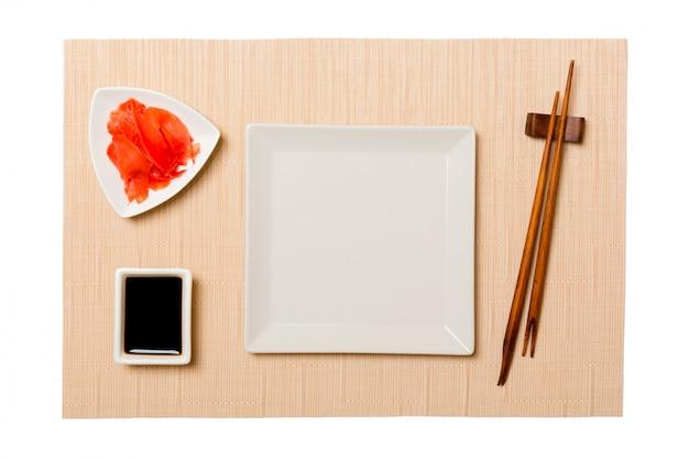 Svuoti il piatto del quadrato bianco con le bacchette per i sushi e la salsa di soia, zenzero sul fondo marrone della stuoia dei sushi. Foto Premium
