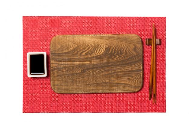 Svuoti il piatto di legno marrone rettangolare con le bacchette per i sushi e la salsa di soia sul fondo rosso dei sushi della stuoia Foto Premium