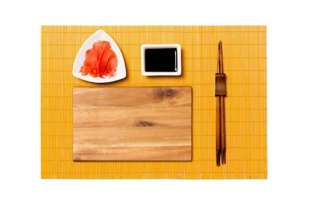 Svuoti il piatto di legno marrone rettangolare con le bacchette per la salsa di sushi, dello zenzero e di soia sulla stuoia di bambù gialla. vista dall'alto con copyspace Foto Premium