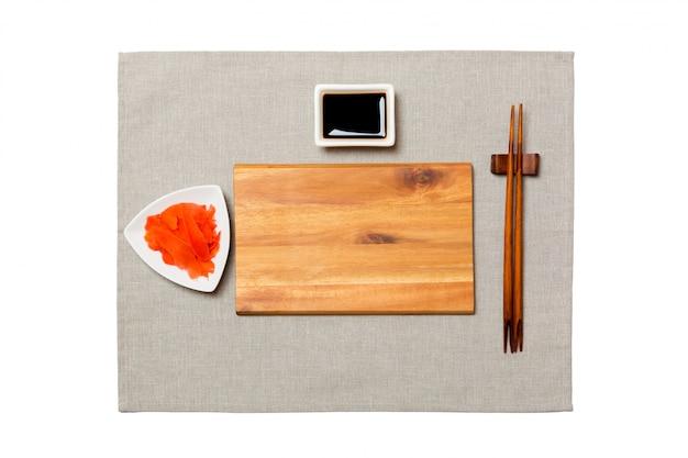 Svuoti il piatto di legno marrone rettangolare con le bacchette per la salsa di sushi, zenzero e soia sul tovagliolo grigio. vista dall'alto con copyspace Foto Premium