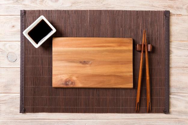Svuoti il piatto di legno rettangolare per i sushi con salsa e le bacchette sulla tavola di legno, vista superiore Foto Premium