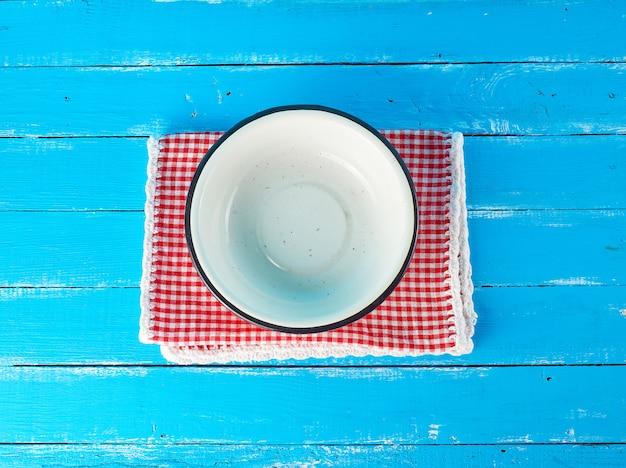 Svuoti il piatto di metallo bianco rotondo su un tovagliolo bianco rosso del tessuto Foto Premium