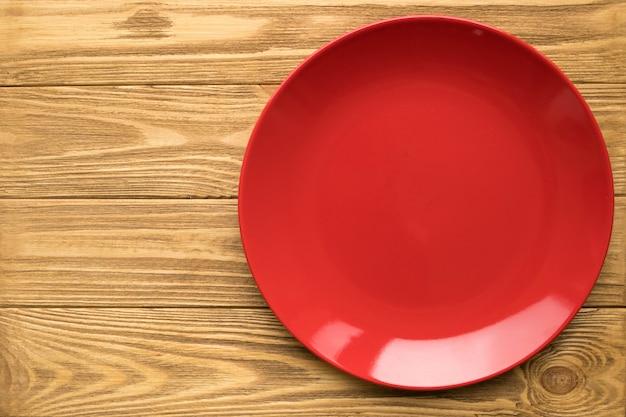 Svuoti il piatto rosso su una tavola di legno, vista superiore Foto Premium
