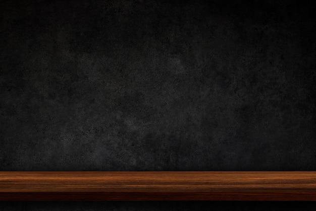 Svuoti la cima degli scaffali di legno sul fondo scuro del muro di cemento Foto Premium