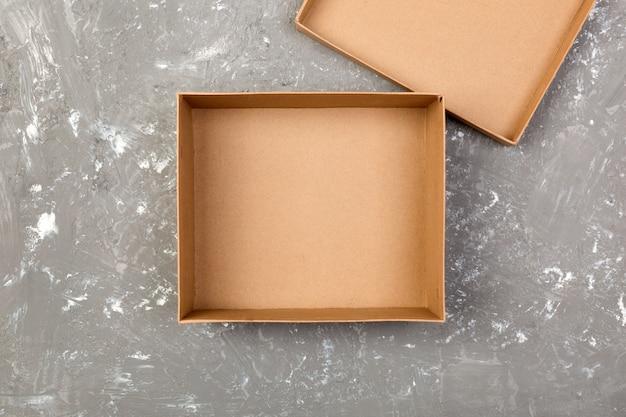 Svuoti la scatola di cartone marrone aperta per derisione sulla tavola grigia del cemento con lo spazio della copia Foto Premium